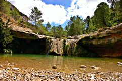 Hidden crystal waterfall in the forest of Spain. Crystal river where you can swim in summer during the hots days in Spain Royalty Free Stock Photo