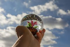 Human Hand Holding a Paperweight. Crystal round paperweight hand held towards the sky at day time Royalty Free Stock Photo