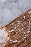 Crystal sea salt on a piece of wood over dark white textured background, top view, close-up, selective focus. Crystal sea salt on a piece of wood over dark Stock Photos