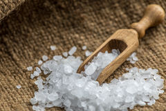 Crystal sea salt. Scoop on a jute background Royalty Free Stock Photos