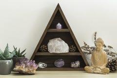 Crystal Shelf triangular con follaje suculento de las plantas y la estatua de madera de Buda fotos de archivo