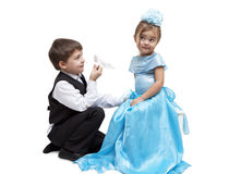 Crystal slipper. Little boy give a glass slipper to little girl Stock Image