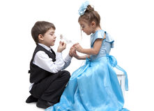 Crystal slipper. Little boy fitting a glass slipper onto a beautiful little girl Stock Images