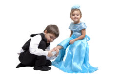 Crystal slipper. Little boy fitting a glass slipper onto a little girl Stock Photography