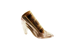 Crystal Slipper with money. Crystal Slipper representing fashion and cinderella-like fantasies filled with Money in the form of many large bills Royalty Free Stock Photo