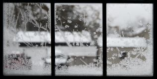 Crystal snowflakes on icy window stock images