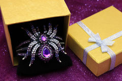 Crystal Spider Jewelry. Purple crystal spider jewel in yellow gift box with glitter bokeh light blur background Royalty Free Stock Images