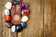 Crystal stones around wood with brass pentagram symbol Royalty Free Stock Images