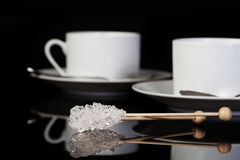 Crystal Sugar Swizzle Sticks. On black reflective surface and two white coffee cups blurred in background Royalty Free Stock Photography