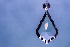 Crystal Teardrop Pendant, Hanging Against A Sky-like Background Royalty Free Stock Image