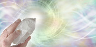 Crystal Therapy Resonance Banner. Female hand pointing a clear quartz terminated crystal upwards on a light pastel rainbow colored  spiraling  vortex background Royalty Free Stock Images