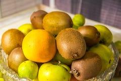 Crystal vas med frukter: kiwi limefrukt, apelsin, äpple Arkivfoto