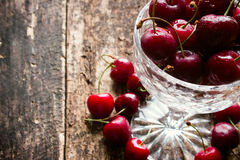 Crystal vase with rustic cherry with water drops on a wooden table Royalty Free Stock Images