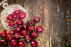 Crystal vase spilling rustic cherry on a wooden table Royalty Free Stock Image