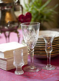 Crystal wine glasses. Three glasses of different shapes on a background of a stack of napkins and plates Stock Photography