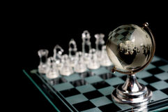 Crystal world chess globe. Crystal chess pieces with a globe in the front.On black background Stock Image