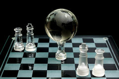 Crystal world chess globe. Crystal chess pieces with a globe in the center.On black background Stock Photo