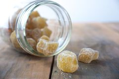 Crystalized ginger sweet spicy snack. Crystalized candied ginger snack poured from glass jar Stock Photos