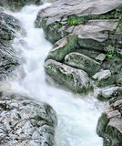 Crystalline mountain stream. Rapid stream among the different big rocks stock images