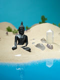 Crystals and buddha statuette miniature landscape. Different types of quantz crystals and a metallic buddha statuette, in a sea shore miniature landscape, with stock photography