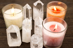 Crystals and color candles. Quartz crystals aligned and lighted color candles Stock Image