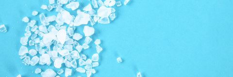 Crystals of large sea salt and dill on a blue table.  stock photo