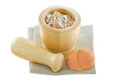 Cáscaras de huevo del pollo al lado de una maja y de un mortero de madera con agolpamiento Foto de archivo