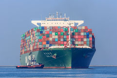 CSCL Venus container ship with tug boats Stock Image