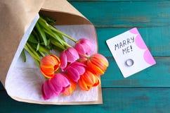 Cáseme nota del mensaje con el anillo de compromiso y florece el ramo Fotografía de archivo libre de regalías