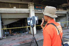 CSI. Crime Scene Investigation officers investigating the burning shopping center with a three-dimensional scanner in the city of Solo, Central Java, Indonesia Stock Photo