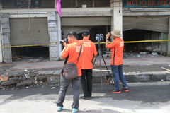 CSI. Crime Scene Investigation officers investigating the burning shopping center with a three-dimensional scanner in the city of Solo, Central Java, Indonesia Royalty Free Stock Images