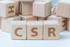 CSR, Collectief Sociaal Verantwoordelijkheidsconcept, houten kubusblok met brieven die acroniem CSR op wit gridlinenotitieboekje  stock foto's