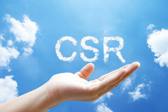 CSR or Corporate Social Responsibility cloud word. Floating on upturned hands in blue sky Royalty Free Stock Photo