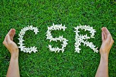 Csr. Flowers arranged in csr shape with supporting hands - corporate social responsibility royalty free stock photos
