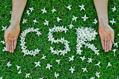 Csr. Flowers arranged in csr shape with supporting hands - corporate social responsibility royalty free stock photo