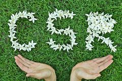 Csr. Flowers arranged in csr shape with supporting hands - corporate social responsibility royalty free stock image