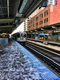 CTA`s pink line train entering the station at Clinton/Adams stop in Downtown Chicago Loop during snowy winter day. Chicago, IL / USA - 2/5/18: CTA`s pink line Stock Images
