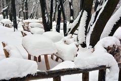 CTables y bancos cubiertos con nieve en el centro turístico del bosque imágenes de archivo libres de regalías