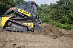 CTL Pushing Dirt. Compact Track Loader (CTL) pushing Dirt Stock Image