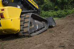 CTL Pushing Dirt. Compact Track Loader (CTL) pushing Dirt Stock Images