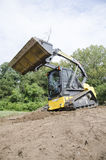 CTL Pushing Dirt. Compact Track Loader (CTL) pushing Dirt Stock Photo
