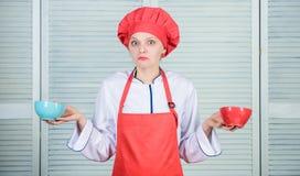 Cuántas porciones usted quisieran comer Cuencos del control del cocinero de la mujer Calcule la caloría de la cantidad usted que  fotografía de archivo libre de regalías