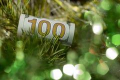 Cuánto hace la Navidad Una cuenta del ciento-dólar se derrumbó con una paja está en las ramas de la picea del ` s del Año Nuevo C Imagenes de archivo