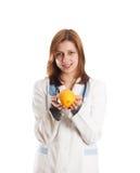 Cuídese en el uniforme médico que sostiene una naranja en sus manos Fotos de archivo libres de regalías
