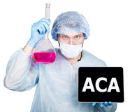 Cuídese en uniforme quirúrgico, sosteniendo el frasco y la PC digital de la tableta con la muestra del aca tecnología, Internet y Imagen de archivo