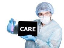 Cuídese en uniforme quirúrgico, sosteniendo el tubo de ensayo y la PC digital de la tableta con la muestra del cuidado tecnología Imágenes de archivo libres de regalías
