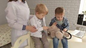 Cuídese y oso de peluche de examen paciente de dos muchachos almacen de metraje de vídeo