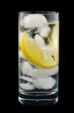 Cuña de limón en el agua mineral de cristal con hielo Imágenes de archivo libres de regalías