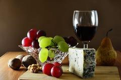 Cuña del queso con sangre azul francés con las uvas y el vino rojo Foto de archivo