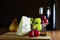 Cuña del queso con sangre azul francés con las uvas y el vino rojo Imagenes de archivo